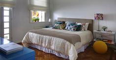 No quarto do casal, as arquitetas Roberta Moura, Paula Faria e Luciana Mambrini apostaram em uma decoração neutra, pincelada pelo colorido das almofadas, do abajur e do pufe amarelo. O apartamento alugado, com 220 m², fica no bairro do Leblon, no Rio de Janeiro (RJ)