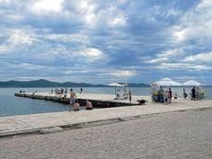 """Pier sobre a Riva em Zadar, Croácia. Este é um destino popular para os visitantes da costa da Dalmácia. No cais de pedra pode-se pegar alguns raios de sol e desfrutar da brisa do mar. """"Riva"""" é um termo usado em toda a Croácia para se referir ao passeio que corre ao longo do Mar Adriático. A Riva em Zadar possui um Órgão do Mar, que reproduz a música das ondas.  Texto e fotografia: Barbara Weibel."""