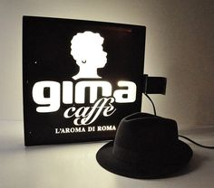 This amazing eye catching black & white wall sign comes from Gima Caffè, a company, based in the capital of Rome - Italy, which offers quality coffee.  The sign is double sided featuring the official logo of the company and looks fantastic when lighted. It has been rewired with a european plug but if you wish we can include an american plug adaptor, just let us know! It is made of plexiglass with wooden frame, the stencilled logo is from vinyl sticker. It does show a few scratches but ove...