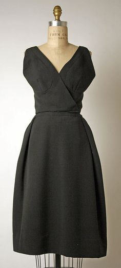 Simple grey wool dress without the over jacket.  1960-61 from the French House of Dior.  Portrait V neckline.  Wrap over bodice.  Sleeveless.  The darts & insets in the bodice pieces help the garment to fit gracefully to the wearer's form.  The skirt has a flat front and falls crisply in a slightly nipped A-line skirt