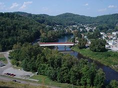 """View of Philippi, county seat of Barbour County, West Virginia, USA. Visible are the historic Philippi Covered Bridge spanning the Tygart Valley River and the main administrative building and chapel of Alderson-Broaddus College atop """"Battle Hill"""" (upper left) overlooking the town."""