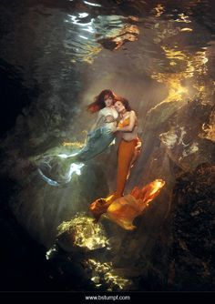 Photo of two red haired twin mermaids swimming together in filtered light under water; one mermaid in a green tail and the other in an orange tail. Filmed in the cenote underwater cave and cavern system near Playa Del Carmen, Mexico. Underwater photography art by Brenda Stumpf. Models Jessica Dru and Virginia Hankins. See more at www.sheroesentertainment.com / www.facebook.com/sheroesentertainment / www.facebook.com/themermaidproject