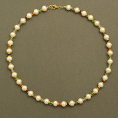Dieses Collier aus weißen Zuchtperlen und verschiedenen Edelsteinen ist eine echte Augenweide an jedem Hals. Durch die abwechselnde Verwendung einer Perle, eines kleinen Goldelements und eines...