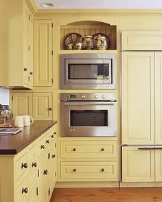 The corner cabinet at the top left opens up fully, while underneath it is a convenient appliance garage to hide away toaster, etc. Open space over microwave adds spot for display (or cookbook collection!).