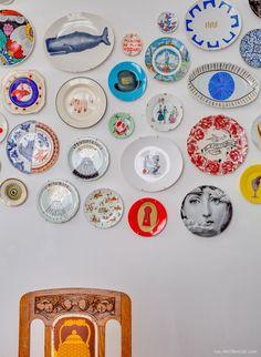 Composição de pratos de diversas marcas e artistas na parede da sala de jantar.