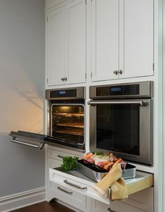 Under white shaker cabinets, side-by-side stainless steel wall ovens are mounted above pull out drawers donning polished nickel pulls and finished with pull out stainless steel countertops.