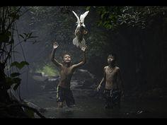Dois garotos tentam pegar um pato em um riacho próximo a uma cachoeira na província de Nong Khai, Tailândia