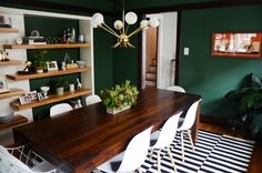 An Eclectic Vintage Chicago Bungalow with a stylish high-impact yet organic dining room. Dark green wall paint (Benjamin Moore Martha's Vineyard), light fixture (Dakyue from Amazon), dining table (West Elm), dining chairs (All Modern), rug (IKEA), unique bookcase (Dania).