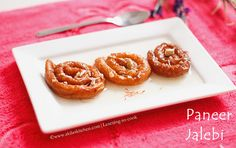 Paneer jalebi - an Indian sweet made with cottage cheese and soaked in sugar syrup. Served with some nuts and saffron.