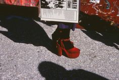 A woman in red heels holds a copy of Aftermath by the Rolling Stones at a market somewhere in Mexico March 1972