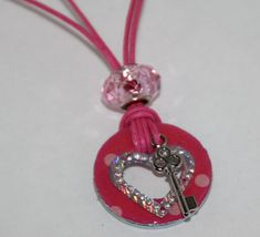 Steel Washer Necklace. Made with Pink and Light Pink Hemp cording (double strand) with lobster claw clasp. Pink Crystal Pandora style bead sits at top of decorative washer. Washer is embellished with foil heart and Key charm. Very fun.. 12 3/4inches long from clasp to bottom of washer. Washer is 1 inch around.