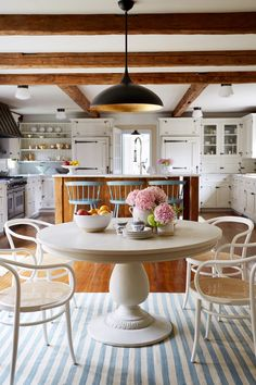 A white pedestal table framed by a striped rug, a gleaming brass pendant light and vintage caned chairs makes sure the focus is on the family when it comes to the kitchen.