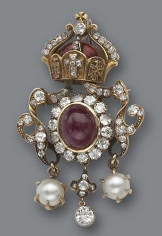 A ruby, diamond and enamel brooch the central oval cabochon ruby within a surround of round brilliant-cut diamonds, accented by a diamond and cultured pearl ribbon-like surround and surmounted by a red enamel and diamond-set crown; estimated total diamond weight: 2.00 carats; mounted in silver and eighteen karat gold. Victorian or Victorian style