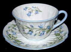 This is a Shelley China, England cup and saucer in the Harebell pattern number 13590 in the low Oleander shape with blue trim. The finely petal molded cup and saucer was made 1950-1966. The bone china