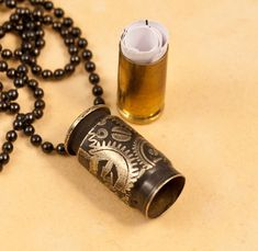 This beautiful time capsule pendant is made from an etched bullet casing. It is a .400 CorBon. It has been etched with our Clockworks design and is finished in bright brass and near black. This is a variation of our most popular piece, only in miniature form. A 9mm Lugar casing is fitted to slide inside and hold your most cherished memories; a love note, thought of the day, favorite saying, or you can just carry a message from Bond, James Bond. The overall length is only 1 plus a crystal and…