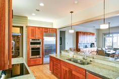 Warm wood cabinets pair with granite countertops for a beautiful, natural look in this contemporary kitchen. A mix of recessed lighting, natural light and glass pendants illuminates the space.