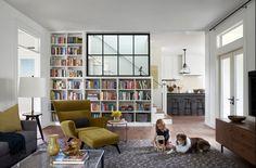 salon moderne aménagé avec un fauteuil verdâtre, un tapis gris et un escalier bibliothèque moderne et fonctionnel