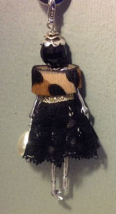 https://www.facebook.com/pages/La-Bella-Dolly-Firenze/199746150223173?ref=hl Pendant in doll shape, 9 inches long, with chain.  Skirt in lace and stole in pony hair.