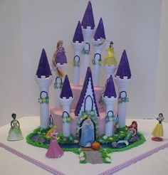 """Disney Princess Castle Cake - I used the Wilton castle kit. I also made modifications to the towers that inserted into the cake by drilling holes and inserting dowel rods secured with hot glue. The directions said to secure dowels with candy melts. For the towers on the cake board I attched them with royal icing plus a ring of fondant and then covered with buttercream """"grass."""" This cake had to be transported and it did just fine. All the princesses are toys. The stones, pumpkin, frog, wood…"""