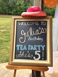 A large vintage easel and sign greet guests to the tea party. - Southern Vintage Table