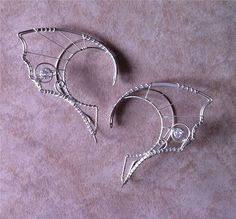 This is a pair of hair-friendly, dragon-style elf ears, made with argentium silver and white topaz set in sterling.