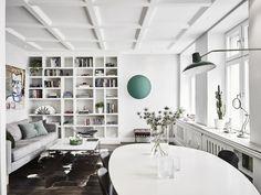 Living room: built-in bookshelves, white walls, white coffered ceiling, IKEA KARLSTAD Isunda grey sofa