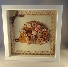 A beautiful handmade hedgehog button art picture. My hedgehog (one of my favourites) made using a selection of beige, cream, light chocolate and soft gold buttons and embellishments. It is mounted on a lovely quality craft paper and card, enhanced with a cotton lace trim. Set in a white box frame with glass to the front for protection. Overall dimensions are 9 1/2 x 9 1/2. A gorgeous gift or treat for your own home for all ages.