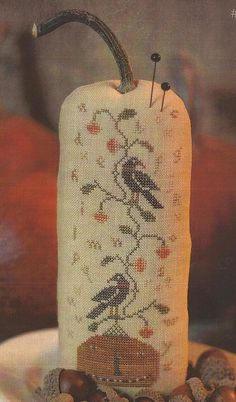 A TALL PRIMITIVE CROSS STITCH PUMPKIN PINKEEP.