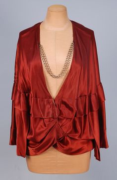 """PAUL POIRET LABELED SILK """"ROMAN JACKET"""", c. 1910. In """"as found"""" condition, burgundy satin short cape with ruffled over-capelet, the  open front having tucked crossing points at waist with single self button & loop closure, the button marked """"La Robuste Paris"""", lined in pale pink silk. Two silver link chains at neckline probably later additions."""