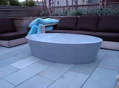Monolithically cast oval coffee table with hollow core for Manhattan rooftop, designed with Nelson Byrd Woltz Architects. #concrete