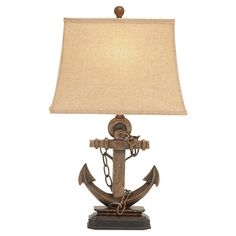 Cast a warm glow over your reading nook or nightstand with this nautical table lamp, featuring an anchor-inspired base and weathered finish for antiqued appe...