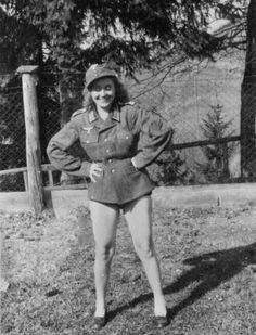 An unidentified apparent sweetheart of a German soldier in some occupied part of Europe strikes a naughty pose wearing German army tunic and field cap.