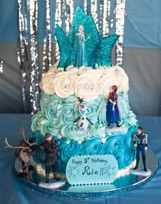 Frozen themed cake for a little girl who's a big fan of Elsa!! It's an eggless vanilla cake with whipped ganache filling and vanilla buttercream frosting. Everything on the cake, except for the 6 toy characters, are edible.