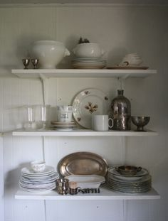 white wooden walls, shelves and funky combination of porcelain with silver