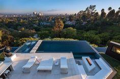 rechteckiger Infinity-Pool und moderne Terrasse mit weißen Möbeln