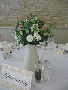 Enamel jugs of pink and cream flowers were used as tablecentres in this wedding.