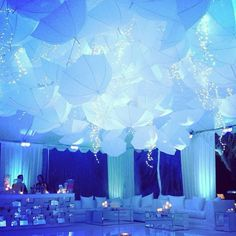 A ceiling of umbrellas and cascading lights for a birthday party. #whitelilacinc