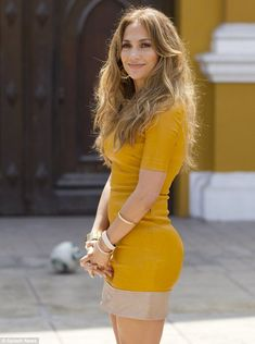 Shining star:Jennifer Lopez shows off her incredible figure in a tight yellow dress as she films her talent show in Lima, Peru