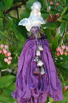 Half doll, at her front is a cabachon rose of French ribbon dangling with buds.
