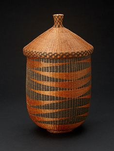 """Tutsi Basket from Rwanda/Burundi.  14.5"""" tall x 8"""" diameter.  The Tutsi women were responsible for weaving baskets, floor mats and wall panels. Basketry weaving was a communal activity which occured during recreational evening gatherings. The black dye comes from boiling banana flowers which creates a black sap. The red dye was was extracted from the root & seeds of the urukamgi plant. www.africaandbeyond.com"""