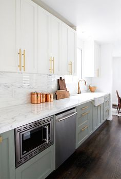 kitchen with top cabinets painted white, Farrow & Ball Wimborne White, and bottom cabinets painted gray, Farrow & Ball Pigeon, accented with brass hardware paired with Calacatta Gold Marble countertops and backsplash. Farmhouse sink paired with gold, gooseneck faucet stands next to stainless steel dishwasher and under the counter microwave.
