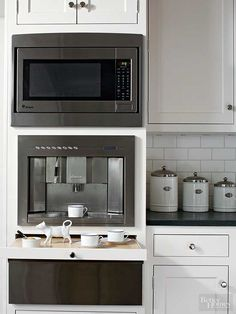 A convenient inset tray pulls out from this base cabinet to accommodate the sugar, cream, cups, and silverware needed for coffee drawn from a built-in espresso maker. The microwave above stands ready to warm milk, cook oatmeal, or heat pastries, making this coffee station the go-to spot at breakfast time./