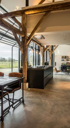 Converting an old barn into a warm industrial farmhouse with big view on an old brick wall, original wooden beams and the beautiful area around the farmhouse.