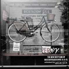 Elementi semplici e comunicativi: tre scale in legno reggono una bici appesa e sullo sfondo la nuova grafica riporta i servizi offerti dalla Bicistazione.