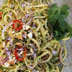 Thai Zucchini Noodle Salad Recipe Salads with zucchini, purple onion, red chili peppers, toasted sesame seeds, toasted almonds, fresh cilantro, kosher salt, red chili peppers, garlic cloves, ginger, green onions, rice vinegar, soy sauce, peanut butter, sesame oil, coconut milk