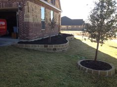 GroundScape, a Fort Worth Landscape Company, installs stone and mortar edging around the flowerbed and tree.