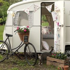Too cute composition with that adorable trailer, bike-with-basket, floral crate, and peeping kitty.
