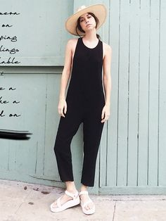 A black jumpsuit is paired with a straw hat and flatforms.