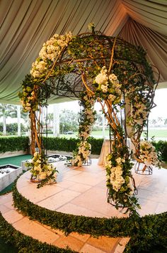 A seemingly stone altar is wrapped in natural greens and holds an ornate asymmetrical chuppah laden with vines.