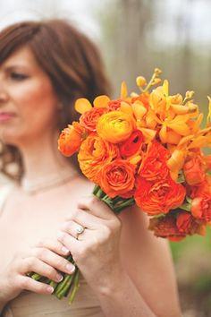Monochromatic orange bouquet of ranunculus, mambo spray roses, poppies, and mokara orchids